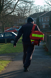 Postman (approaching his 60s) walking briskly as he works, Reading; UK; Dec, 2008,