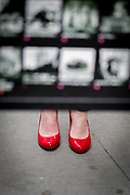 A couple of feet with red shoes are seen below a street guide of the NYSE Euronext Stock Exchange and Wall Street area.