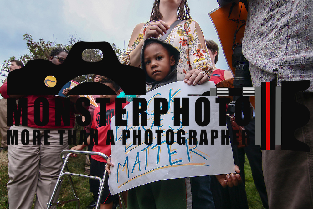 "Jah'kiar Hartley (6) holds a sign that reads ""Black Lives Matter"" while hearing a hoodie during a rededication ceremony Sunday, August 21, 2016, at First Unitarian Church in Wilmington."
