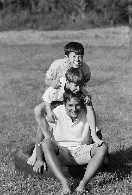 man with two boys playing outdoors