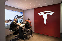 Customers inside Tesla electric car showroom on Kurfurstendamm, Kudamm, in Charlottenburg, Berlin, Germany
