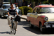 A man rides his bicycle as he passes old American cars on the street of Baracoa, Cuba on Monday July 14, 2008.