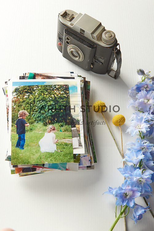 Stack of photographs and vintage camera with flowers