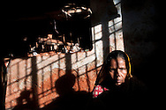 A woman in a brick yard gives the camera an intense stare and harsh afternoon light in Chittagong, Bangladesh.