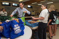 "Mayor Michael Seymour and Diane Pinkham pack up ""Got Lunch"" bags for the first week's deliveries Wednesday morning in the Congregational Church.  (Karen Bobotas/for the Laconia Daily Sun)"