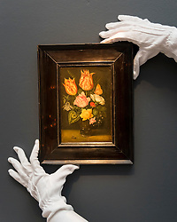 "© Licensed to London News Pictures. 02/12/2016. London, UK. A technician shows ""Still life of tulips, wild roses, cyclamen, yellow ranunculus, forget-me-not and other flowers, in a glass beaker"" by Ambrosius Bosschaert the Elder (est. GBP0.9-1.2m), at a preview of Sotheby's upcoming Old Masters Evening Sale in New Bond Street. Photo credit : Stephen Chung/LNP"