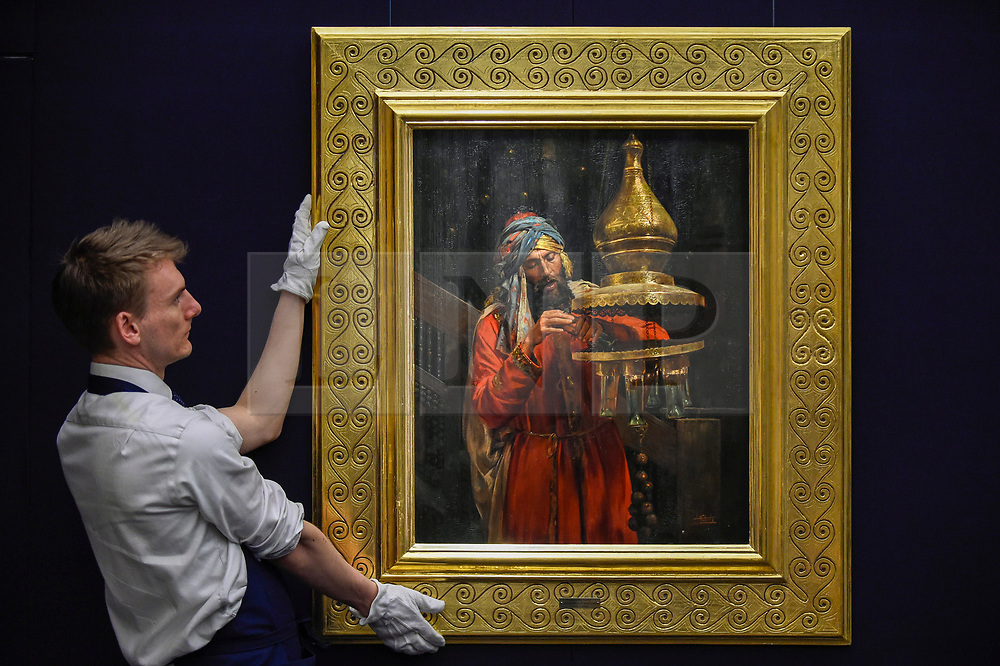 """© Licensed to London News Pictures. 11/10/2019. LONDON, UK. A technician presents """"Lighting the Lamp"""", by Antonio Fabrés Y Costa, (Est GBP100-150k).  Preview of works from the Najd Collection of orientalist paintings at Sotheby's in New Bond Street, which record daily life in the historic Arab, Ottoman and Islamic worlds  All 155 paintings are on public view 11- 15 October, with 40 works to be auctioned on 22 October.  Photo credit: Stephen Chung/LNP"""