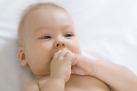 Infant child chewing fists