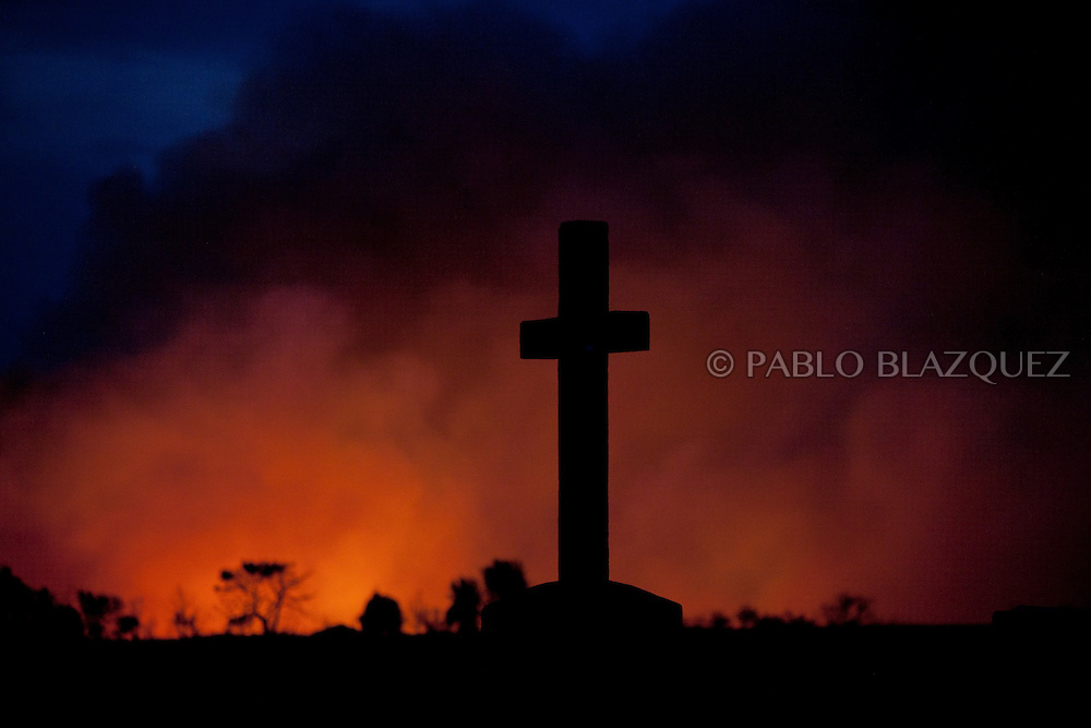 A cross is seen in front of a forest fire near El Cubillo de Uceda, on August 11, 2012 in Guadalajara, Spain. During a heat wave dozens of forest fires have appeared in Spain, three of them at National Parks, like Teide, Doñana or Cabañeros, and thousands of people had to be evacuated at La Gomera and Tenerife, in the Canary Islands.
