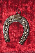 decorated silver horseshoe amulet on red velvet background