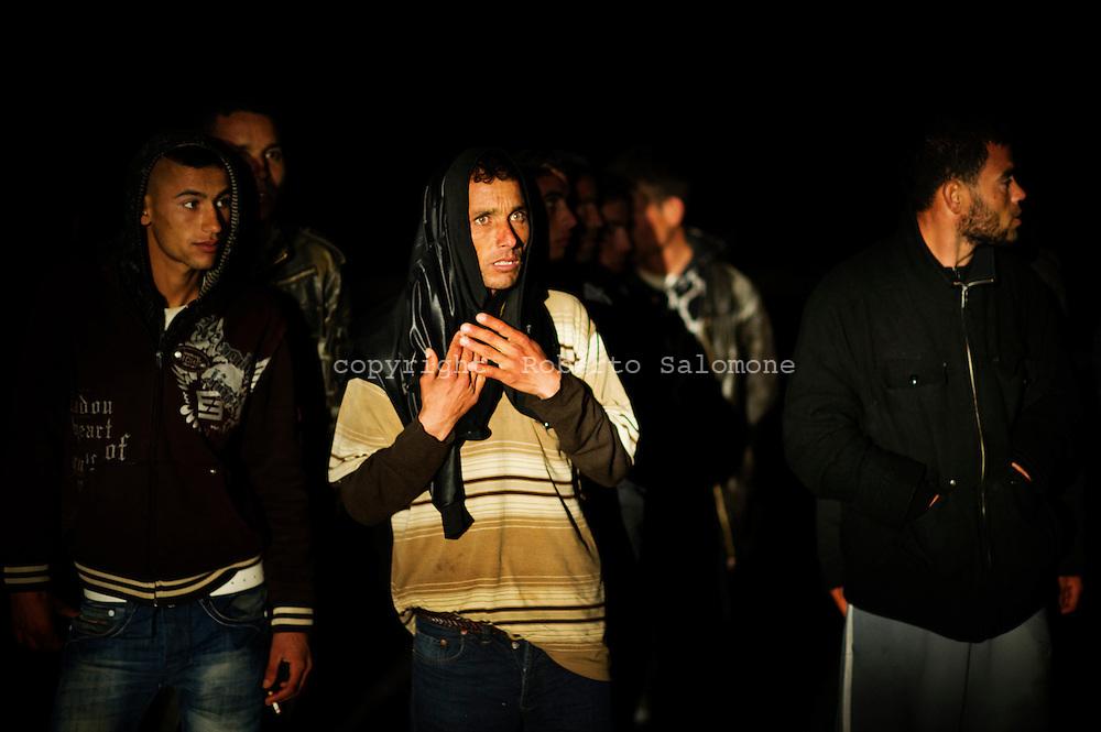 Lampedusa, Italia - 19 marzo 2011. Immigrati appena sbarcati sull'isola di Lampedusa aspettano di essere trasferiti in un centro di accoglienza temporanea..Ph. Roberto Salomone Ag. Controluce