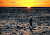 Hawaii, South Pacific.  A lone paddler on the ocean as the sun goes down.