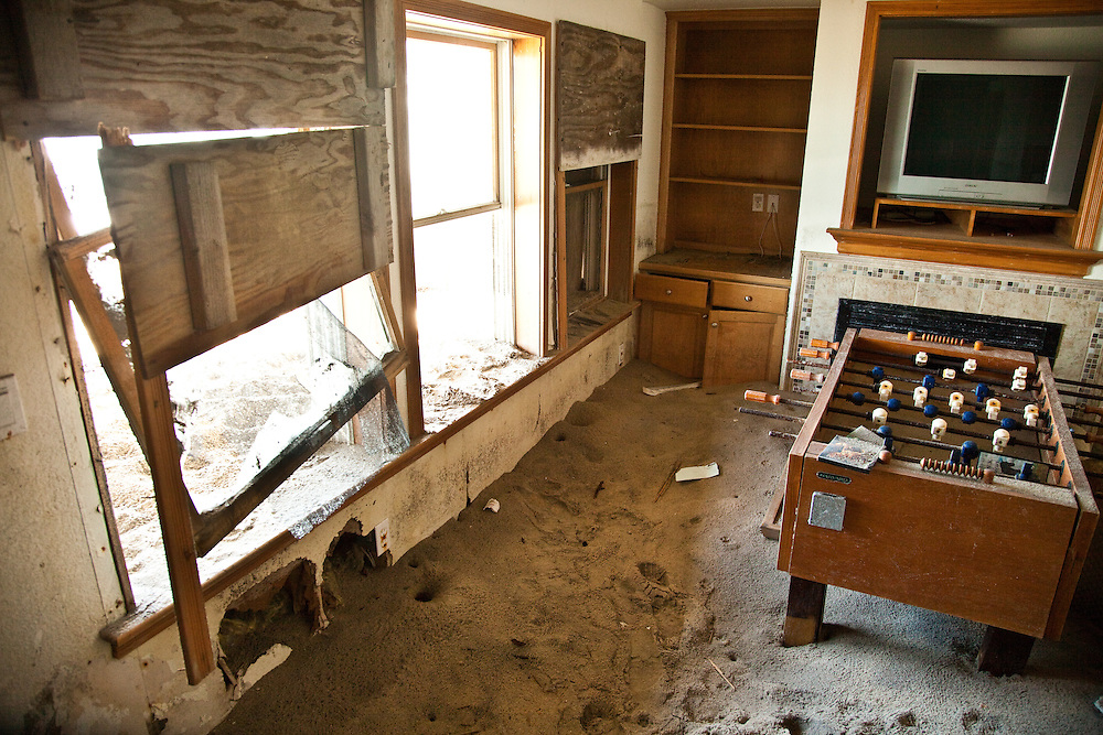Hurricane Irene brought water and sand through the broken windows. The rooms on the first floor are still up to a foot high covered with sand. Furniture and electronic equipment is still there.