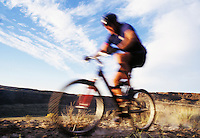 Blur shot of a man riding a mountain bike in a desert canyon.  Frenchmans Coulee near Vantage, Washington, USA<br />