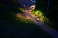 Two couples on a bike path late at night during the Midsummer Night celebrations in Leksand, Sweden