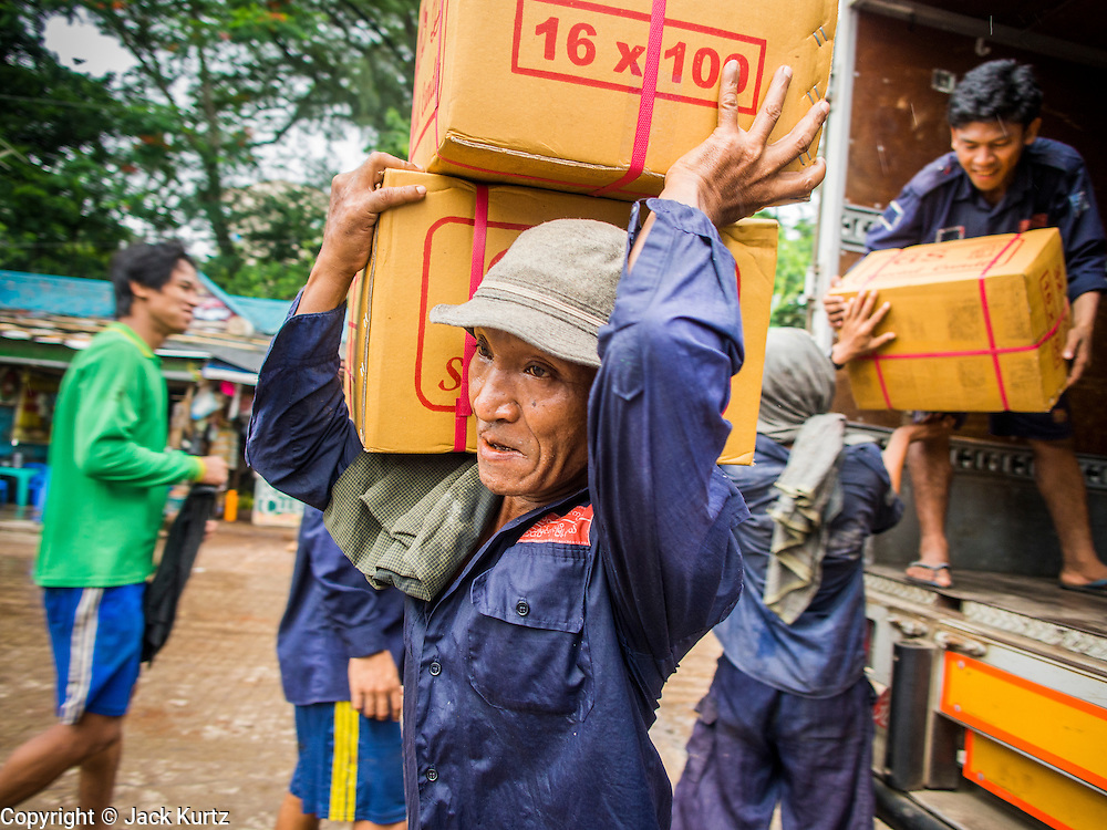 "10 JUNE 2014 - YANGON, MYANMAR:   Porters carry boxes candles to a waiting river boat on the banana jetty. The ""banana jetty"" is on the Yangon River north of central Yangon on Strand Road. Bananas, coconuts and other fruit are brought in here from upcountry, sold and reshipped to other parts of Myanmar (Burma). All of the labor here is done by hand. Porters carry the produce to the jetty and porters load the boats before they steam upriver.   PHOTO BY JACK KURTZ"