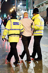 © licensed to London News Pictures. Manchester, UK 01/01/2012. New Years Day revellers in Manchester. Police walk either side of and support a man who is unable to stand up unaided. Please see special instructions for usage rates. Photo credit should read Joel Goodman/LNP