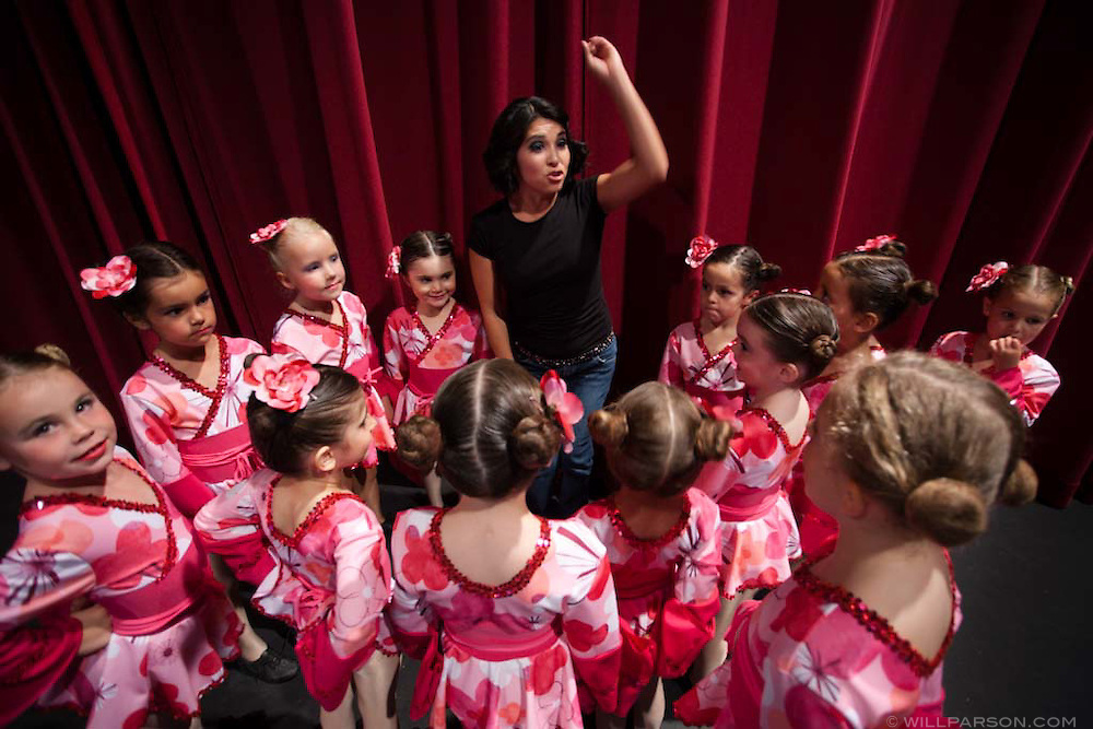 An instructor shares words of inspiration with young pupils of the Royal Dance Academy before their recital on June 26.