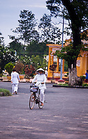 A female worshipper riding her bicycle home after the Cao Dai service at the Holy See in Tay Ninh.