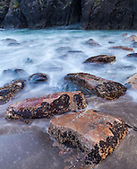 Large flat rocks lead through the rising tide to a dark sea arch in a rock wall, Harris State Beach