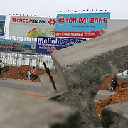 Billboards rise out of rice paddies along a dusty stretch of highway under construction near Thang Long Industrial Park, outside Hanoi, Vietnam, Monday, 03 April 2006.