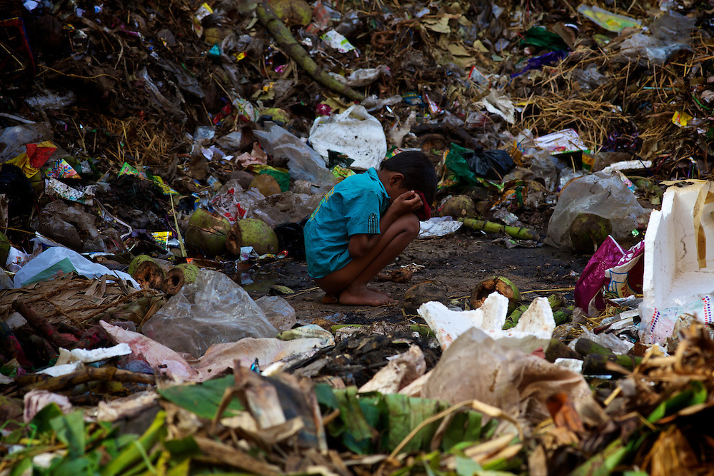 Poor boy between the stacks of garbage in Bangalore. Every day hundreds of millions of people in India wake up at dawn and work hard until sunset to find their way out of poverty. Many of these people cannot access clean water and electricity, nor pay school fees for their children or see a doctor when they are sick. Their basic needs have been largely unmet, neither by public services nor by the market that doesn't consider them as potential customers. Access to health care services in India by low-income people is limited due to the poor supply from the public service, especially in remote areas such as slums.