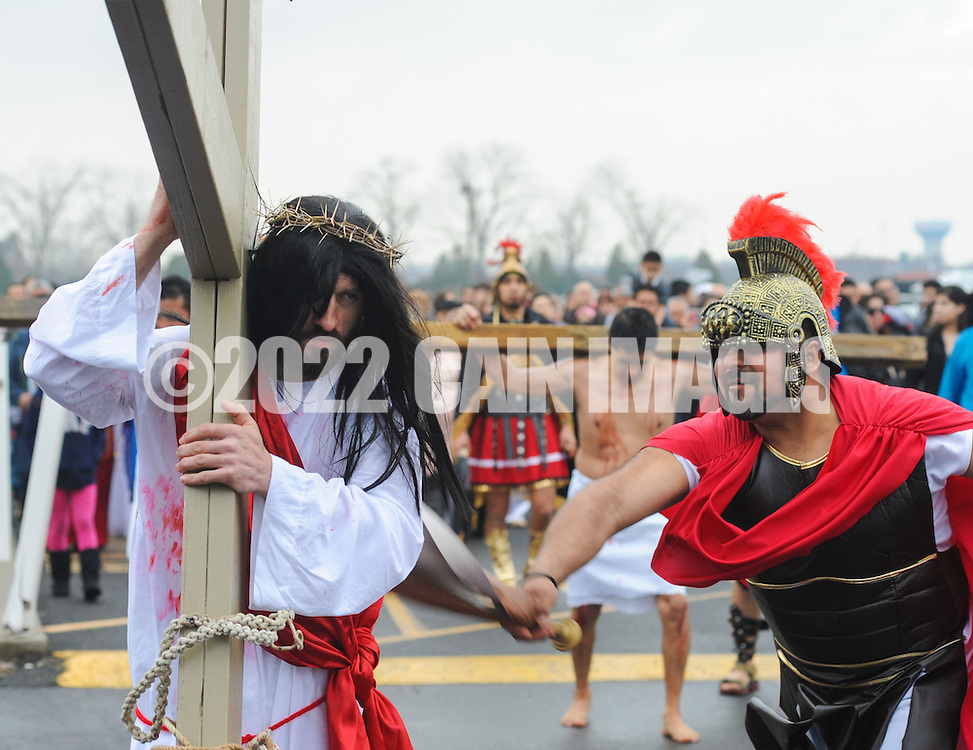Roberto Marquez, of Bensalem, Pennsylvania portrays Jesus as he is beaten by guards while carrying a cross during the Stations of the Cross leading to his crucifixion on Good Friday April 3, 2015 at Our Lady of Fatima in Bensalem, Pennsylvania.  (Photo by William Thomas Cain/Cain Images)