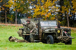 Pickering War Weekend 2009 A member of the Northern World War Two Associations 101st Airborne Living History Group returns fire from a Willys Jeep after being ambushed by enemy troops. Large large battle reenactment <br />