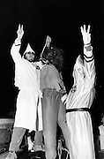 "Flashing the ""W"" or ""white power"" symbol, Ku Klux Klan members simulate the lynching of an African American with a gorilla masked dummy at a Klan Rally outside Jackson, Georgia. The rally - held in a rural farm field - attracted about 125 people and attempted to both incite violence against blacks and enlarge the local KKK membership."