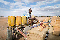 Adan Isscak, Wajir, North Eastern Kenya. Adan fills water up in yellow jerrycans from a deep well, and sells the water around town.