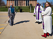 """05 APRIL 2020 - DES MOINES, IOWA:  Rev. BONNIE PARKER, right, and Rev. RUSSELL LACKEY, center, talk to a parishioner after a drive through Palm Sunday service sponsored by Luther Memorial Church on the campus of Grand View University in Des Moines. About 150 people attended the service. They remained in their cars while the ministers read a short passage from the Bible, handed out palms and blessed them. On Sunday, 05 April, Iowa reported 868 confirmed cases of the Novel Coronavirus (SARS-CoV-2) and COVID-19. There have been 22 deaths attributed to COVID-19 in Iowa. Restaurants, bars, movie theaters, places that draw crowds are closed until 30 April. The Governor has not ordered """"shelter in place"""" but several Mayors, including the Mayor of Des Moines, have asked residents to stay in their homes for all but essential needs. People are being encouraged to practice """"social distancing"""" and many businesses are requiring or encouraging employees to telecommute.        PHOTO BY JACK KURTZ"""