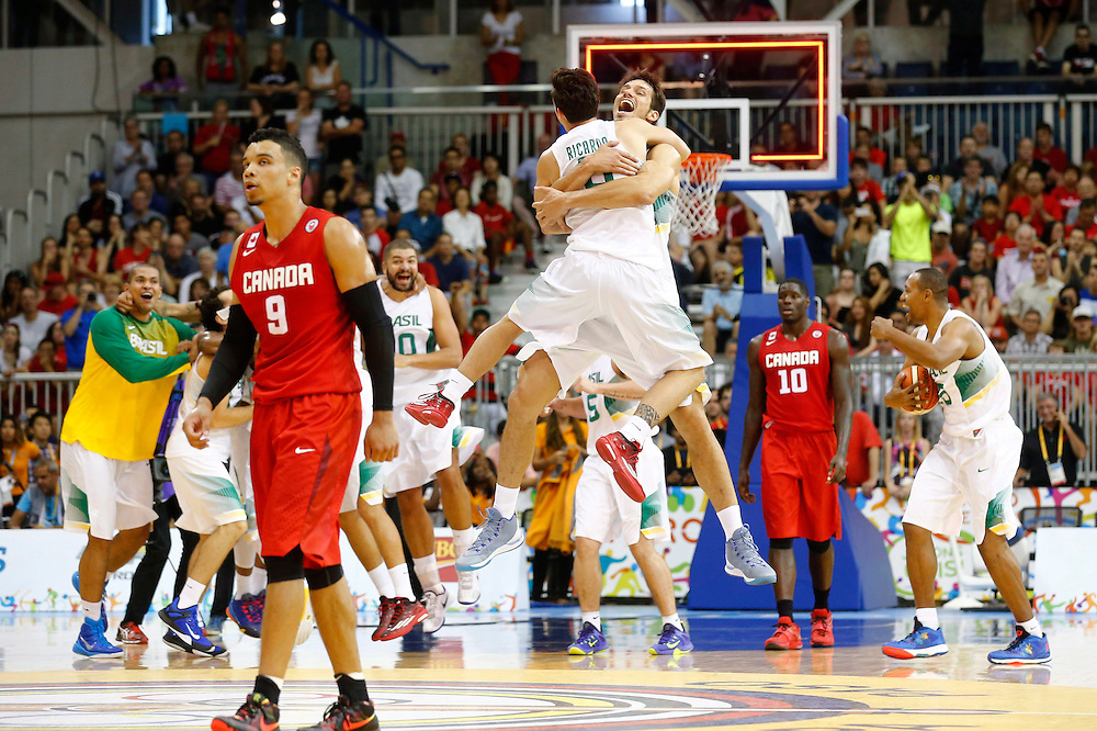 Canada's Dillon Brooks (9) walks off the court as Brazil celebrates winning the gold medal in men's basketball at the Pan Am Games in Toronto, Saturday July 25, 2015.