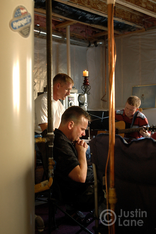 Gordon Harrell, a 1st Lieutenant in the United States Air Force, at center in dark shirt, leads a prayer at the conclusion of a bible study in his basement in Colorado Springs, CO on Wednesday July 13, 2005.  All of the attendees at the bible study are members of New Life Church, a local mega church that has 11,000 members and is led by pastor Ted Haggard.