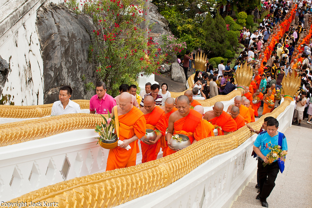 """15 JULY 2011 - PHRA PHUTTHABAT, SARABURI, THAILAND:   Monks make the final ascent to the temple up a flight of stairs during the Tak Bat Dok Mai at Wat Phra Phutthabat in Saraburi province of Thailand, Friday, July 15. Wat Phra Phutthabat in Phra Phutthabat, Saraburi, Thailand, is famous for the way it marks the beginning of Vassa, the three-month annual retreat observed by Theravada monks and nuns. The temple is highly revered in Thailand because it houses a footstep of the Buddha. On the first day of Vassa (or Buddhist Lent) people come to the temple to """"make merit"""" and present the monks there with dancing lady ginger flowers, which only bloom in the weeks leading up Vassa. They also present monks with candles and wash their feet. During Vassa, monks and nuns remain inside monasteries and temple grounds, devoting their time to intensive meditation and study. Laypeople support the monastic sangha by bringing food, candles and other offerings to temples. Laypeople also often observe Vassa by giving up something, such as smoking or eating meat. For this reason, westerners sometimes call Vassa the """"Buddhist Lent."""" The tradition of Vassa began during the life of the Buddha. Most of the time, the first Buddhist monks who followed the Buddha did not stay in one place, but walked from village to village to teach. They begged for their food and often slept outdoors, sheltered only by trees. But during India's summer rainy season living as homeless ascetics became difficult. So, groups of monks would find a place to stay together until the rain stopped, forming a temporary community. Wealthy laypeople sometimes sheltered monks on their estates. Eventually a few of these patrons built permanent houses for monks, which amounted to an early form of monastery.     PHOTO BY JACK KURTZ"""