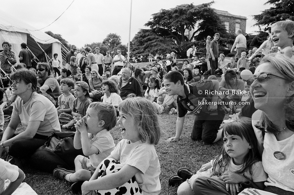 "A crowd of Londoners laugh during an afternoon's Punch and Judy show at The Lambeth Show in Brockwell Park, Herne Hill, England. Children of all ages along with parents grin at the out-of-sight puppet entertainment during this public festival of amusements and stalls in London's inner-city. Only one young girl sits unimpressed at the standard of comedy. She sits with her mother looking serious while the kids nearby roar with laughter - hugely involved with the show. From a personal documentary project entitled ""Next of Kin"" about the photographer's two children's early years spent in parallel universes. Model released."
