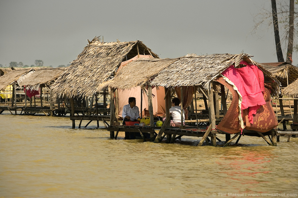 Tourists relax on bamboo platforms at the water's edge at Tonle Bati, a lake near Phnom Penh, Cambodia.