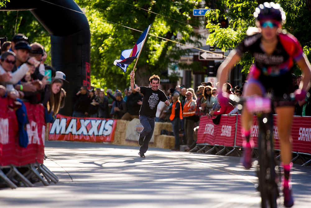 Kaolin Cummins carries the Colorado state flag at the end of the women's fat tire crit Friday.