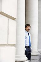 Businessman standing outside building by pillar portrait