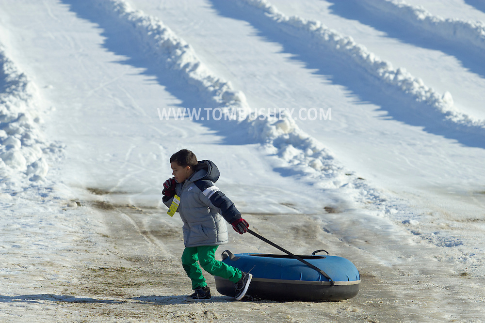 Hamptonburgh, New York - A boy pulls his tube across the bottom of the snow tubing hill at Thomas Bull Memorial Park on Jan. 6, 2013.