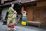 Miehina, a 20 year old maiko ( an apprentice geisha) from the Miyagawacho district of Kyoto, passes an establishment where girls can pay to dress up, and be photographed, as 'geisha' girls, Kyoto, Japan, Sunday, May 18th 2008.
