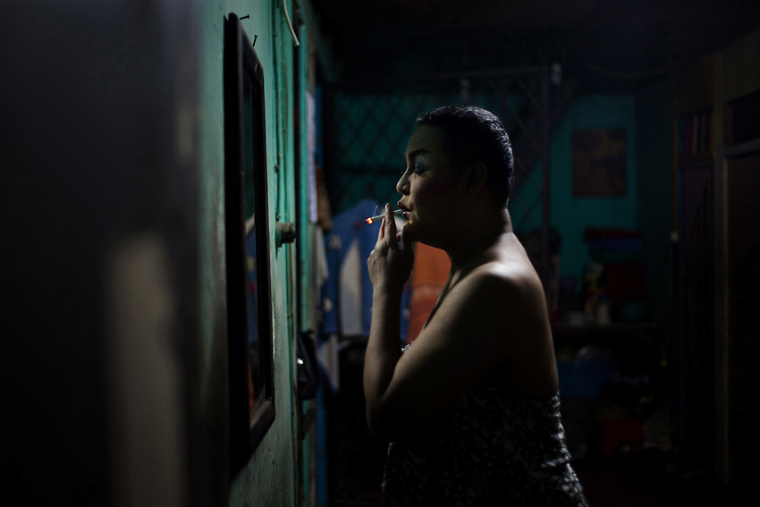 JAKARTA, INDONESIA, MARCH 2013: Mami Joyce takes a cigarette break halfway through the make up process.