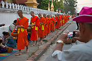 Luang Prabang, Laos. Every morning at dawn, Buddhist monks walk down the streets collecting food alms from devout, kneeling Buddhists, and some tourists. They then return to their temples (also known as wats) and eat together. This procession is called Tak Bat (Making Merit).