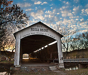 "Mecca Covered Bridge (150 feet long) was built in Burr Arch style over Big Raccoon Creek in 1873 by J.J. Daniels in historic Parke County, Indiana, USA. Golden sunset light beckons at the far opening. Puffy white clouds decorate the blue sky. The traditional ""Cross this bridge at a walk"" sign required slow vehicle speed, but traffic is now diverted to an adjacent modern bridge. Panorama stitched from 2 photos."