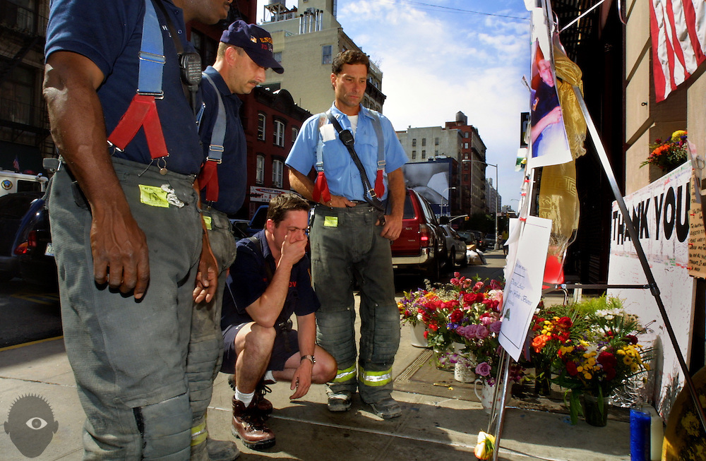 (Center to right) New York Firefighters Bob Peters and Cpt. Charlie Vella join others in reading a tribute outside of the station house dedicated to their lost brothers. Still a very difficult thing for them to deal with even though they are back to work at Engine Co. 18 in Manhattan.