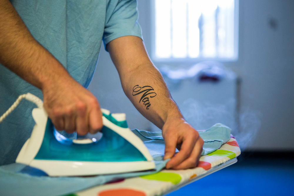 A prisoner ironing his t-shirt the the corridor ready for a family visit, he has 'Nan' tattooed on his arm. Beaufort House, a skill development unit for enhanced prisoners. Part of HMP/YOI Portland, a resettlement prison with a capacity for 530 prisoners.© Prisonimage.org Any image use must be agreed first. All images must be credited.
