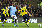 Bernado Silva (20) of Manchester City challenges Alex Gorrin (6) of Oxford United during the EFL Cup match between Oxford United and Manchester City at the Kassam Stadium, Oxford, England on 18 December 2019.