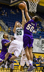 December 29, 2009; Berkeley, CA, USA;  Furman Paladins forward Chris Toler (50) blocks a shot from Utah Valley Wolverines guard Eric Dearden (20) during the second half at the Haas Pavilion.  Furman defeated Utah Valley 77-69.