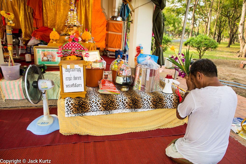 20 FEBRUARY 2013 - PHUTTHAMOTHON, NAKHON PATHOM, THAILAND:     A man prays in Phutthamonthon Buddhist Park in Phutthamonthon district, Nakhon Pathom Province of Thailand, west of Bangkok. The centerpiece of the park is a 52 foot high Buddha statue, which is said to be the highest free-standing Buddha statue in the world.       PHOTO BY JACK KURTZ