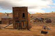A large beam supports the remains of the Swazey Hotel in the historic ghost town of Bodie, CA.