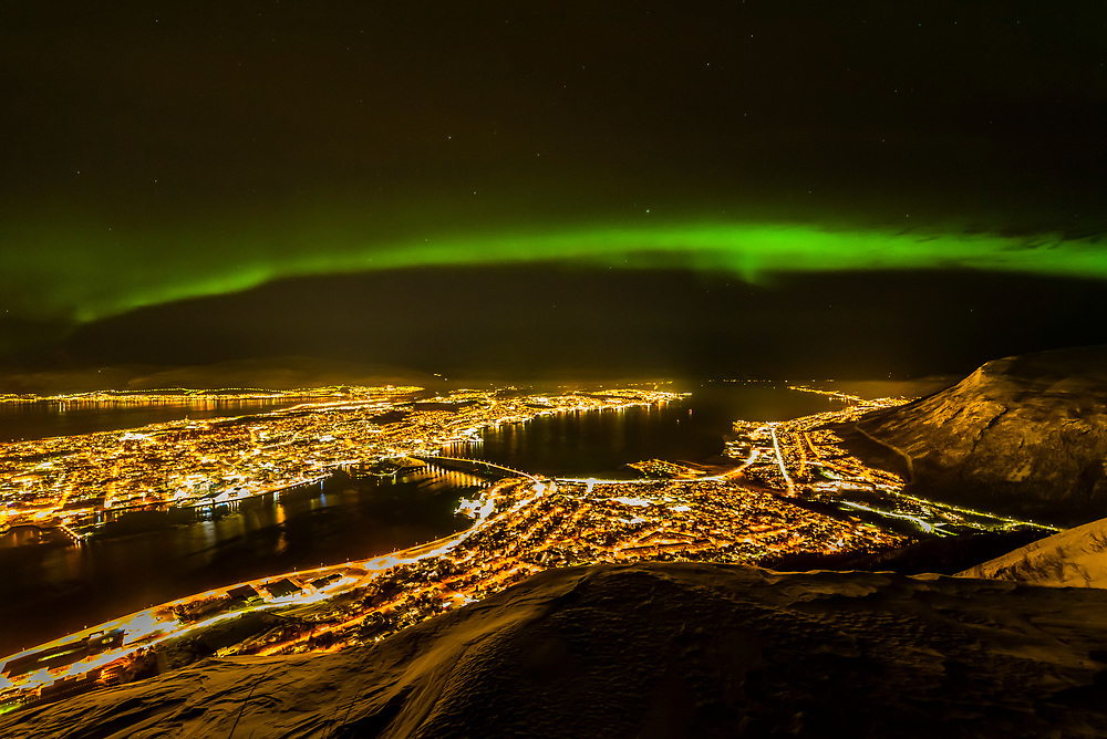 Northern lights (Aurora Borealis) in the sky above the city of Tromso, Norway. Seen from the top of the Fjellheisen  aerial tramway. Tromso sits 217 miles north of the Arctic Circle and is the largest city in Northern Norway.